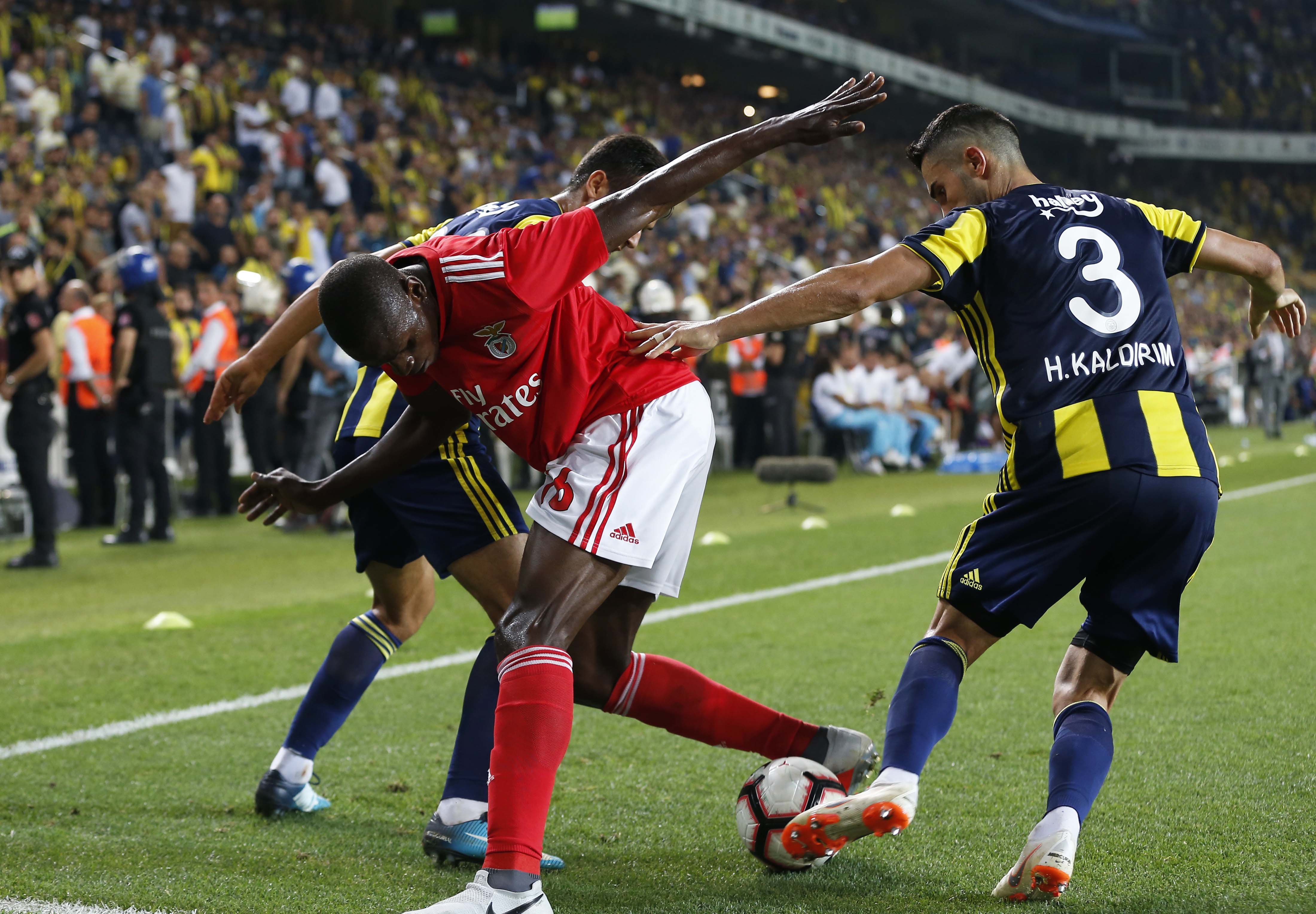 Benfica's Alfa Semedo (left) fights for the ball with Fenerbahce's Baris Alici and Hasan Ali Kaldirim (right) during the Champions League third qualifying round, second leg, soccer match between Fenerbahce and Benfica at the Sukru Saracoglu stadium in Istanbul on Tuesday.