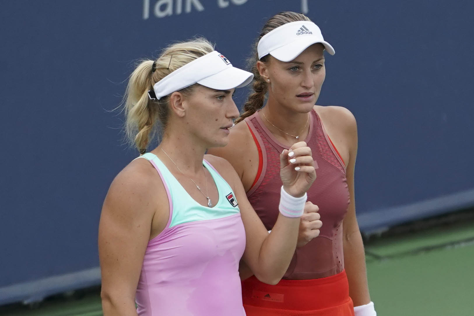 Timea Babos (left) of Hungary, prepares with her partner Kristina Mladenovic (right) of France, during a doubles match against Ekaterina Makarova, of Russia, and Lucie Hradecka, of the Czech Republic, at the Western & Southern Open tennis tournament on Friday in Mason, Ohio.