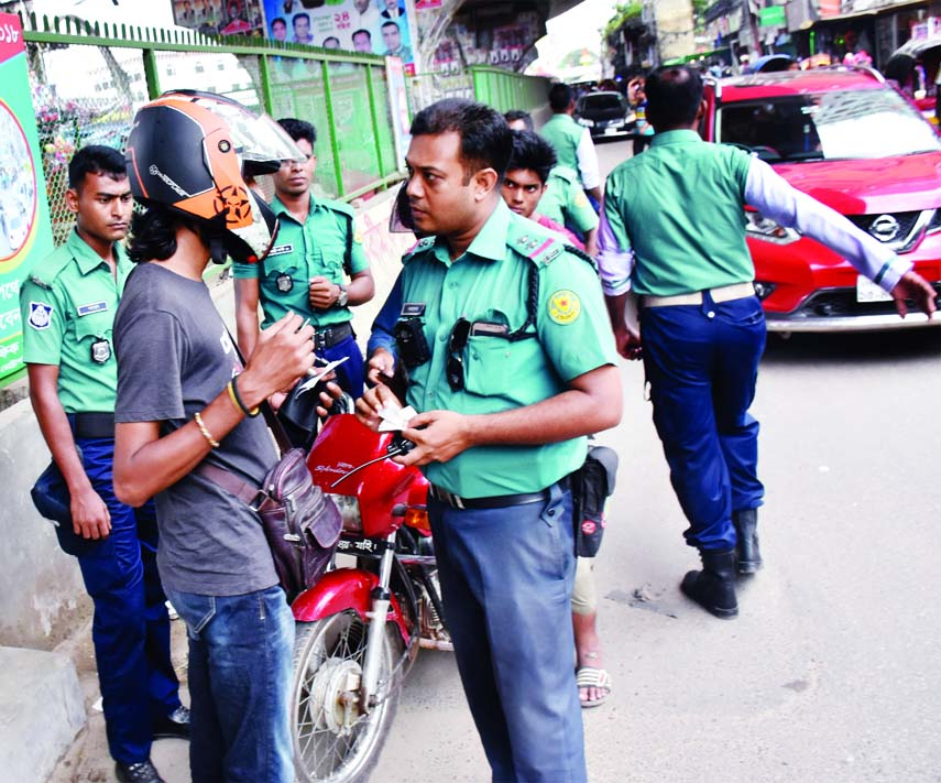Law enforcers seen to cheque documents of the motorized vehicles to ensure safe road. The snap was taken from in front of the city's Rajdhani Super Market on Monday.