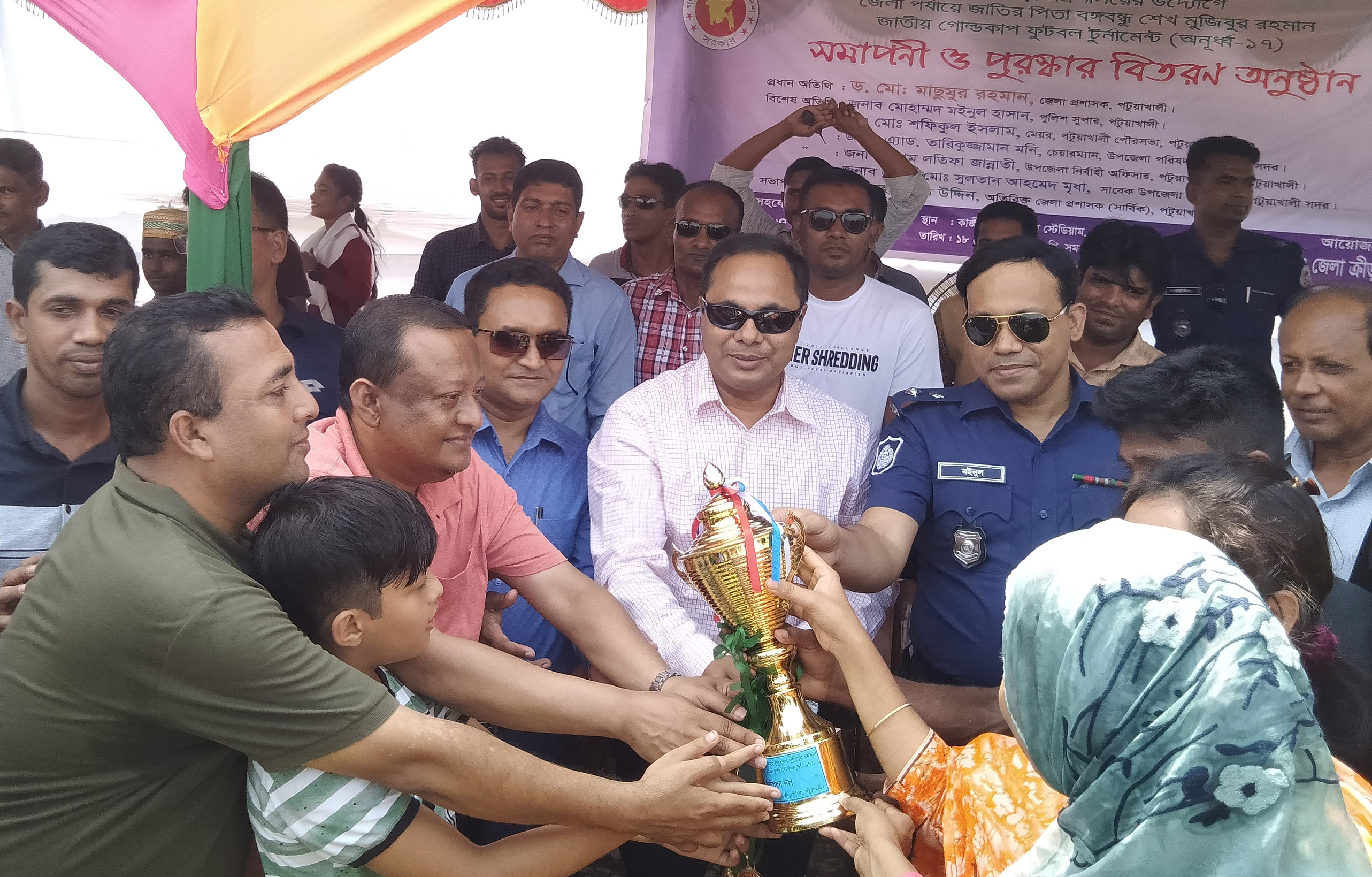 DC of Patuakhali District Dr Masumur Rahman handing over the trophy to Patuakhali Sadar Upazila Football team, which emerged as the champions of the district level of the Bangabandhu Sheikh Mujibur Rahman National Gold Cup Football (Under-17) Tournament at Advocate Abul Kashem Stadium in Patuakhali on Tuesday.