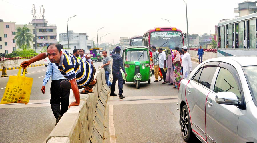 Despite ban on movement over flyovers, pedestrians are seen passing through Hanif Flyover risking their lives. The photo was taken from Jatrabari area on Wednesday.