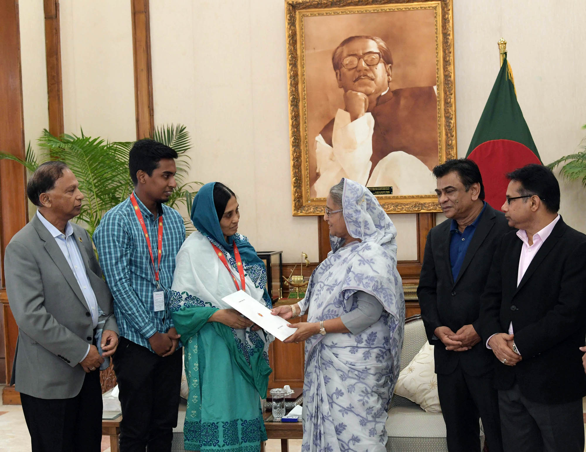 Prime Minister Sheikh Hasina handing over the permanent allotment letter of a flat to Fahmida Rahman, wife of former national hockey player late Zahidur Rahman Pushkin at the Gono Bhaban in the city on Thursday. President of BFF Kazi Salahuddin, Senior Vice-President of BFF Abdus Salam Murshady, Secretary of Youth and Sports Affairs of Bangladesh Awami League Harun-ur-Rashid were present at the time.