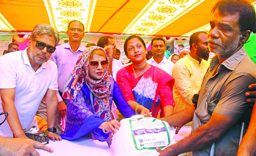 Zainul Haque Sikder, Chairman of Sikder Group and National Bank Limited along with Sanjida Yeasmin, UNO of Naria Upazila of Shariatpur district distributing relief items among the river erosion affected people at the Upazila recently. Parveen Haque Sikder, EC Chairperson, senior officials of the Bank and local elites were also present.