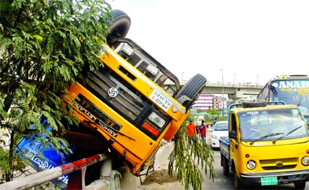 A covered van overturned due to reckless driving near Kuril Flyover on Monday injuring the driver and his helper.
