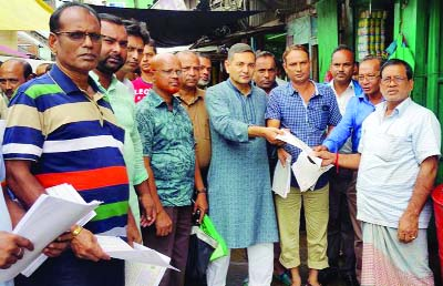 BETAGI(Barguna): Alhaj A B M Golum Kabir, Mayor, Betagi Pourashava distributing leaflet in front of Party Office during an election campaign  for upcoming 11th Parliamentary Election on Saturday.