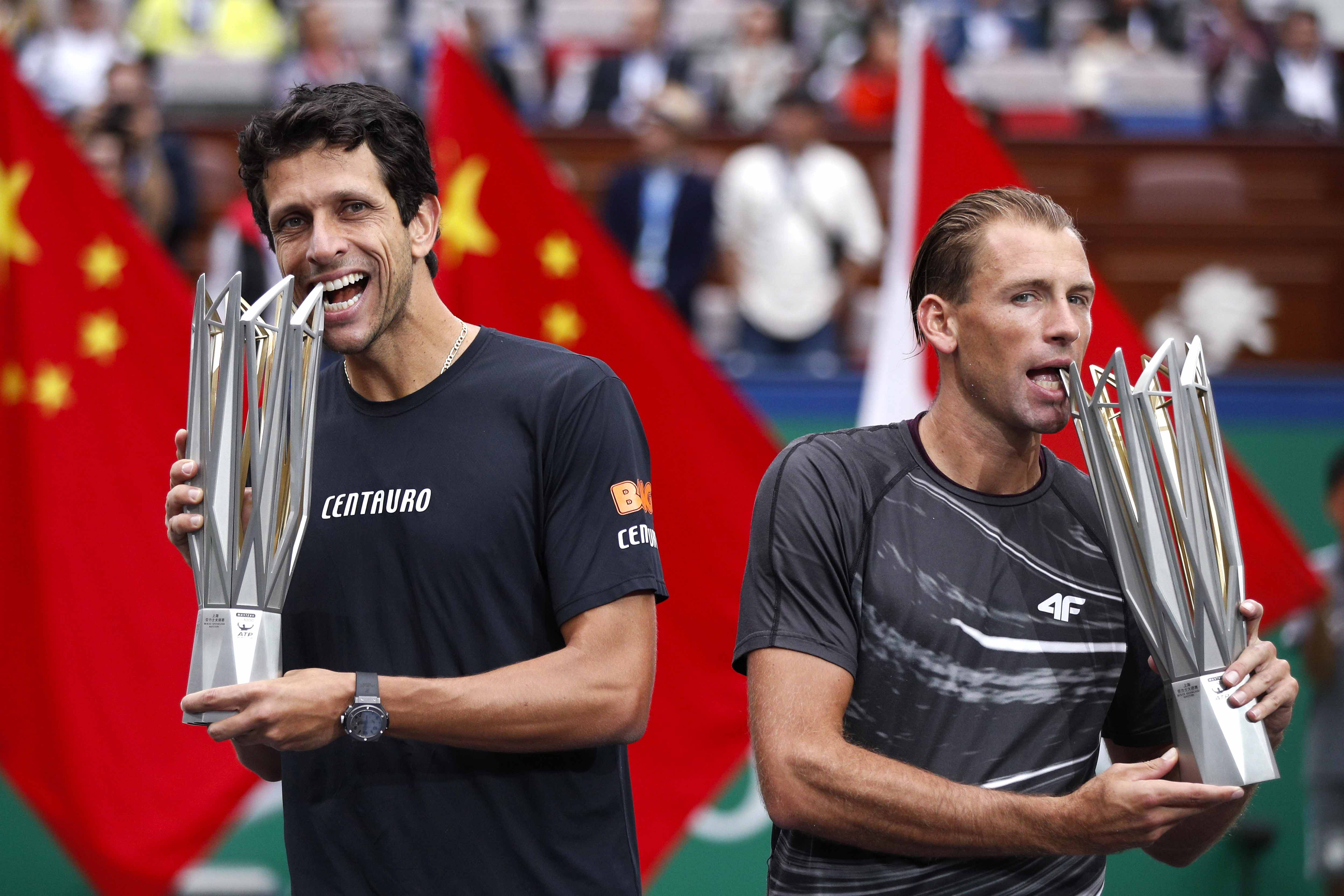 Marcelo Melo of Brazil (left) and his partner Lukasz Kubot of Poland bite their winning trophy as they pose for photographers after beating Jamie Murray of Britain and Bruno Shares of Brazil in the men's doubles final match of the Shanghai Masters tennis tournament at Qizhong Forest Sports City Tennis Center in Shanghai, China on  Sunday.
