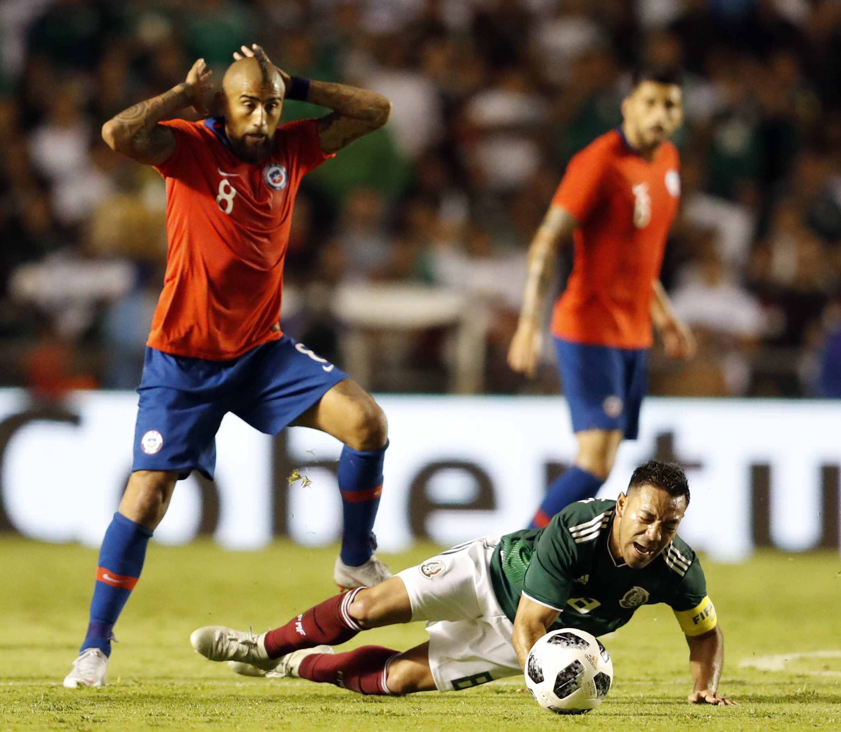 Chile's Arturo Vidal (left) fouls Mexico's Marco Fabian during a friendly soccer match between Mexico and Chile, in Queretaro, Mexico on Tuesday.