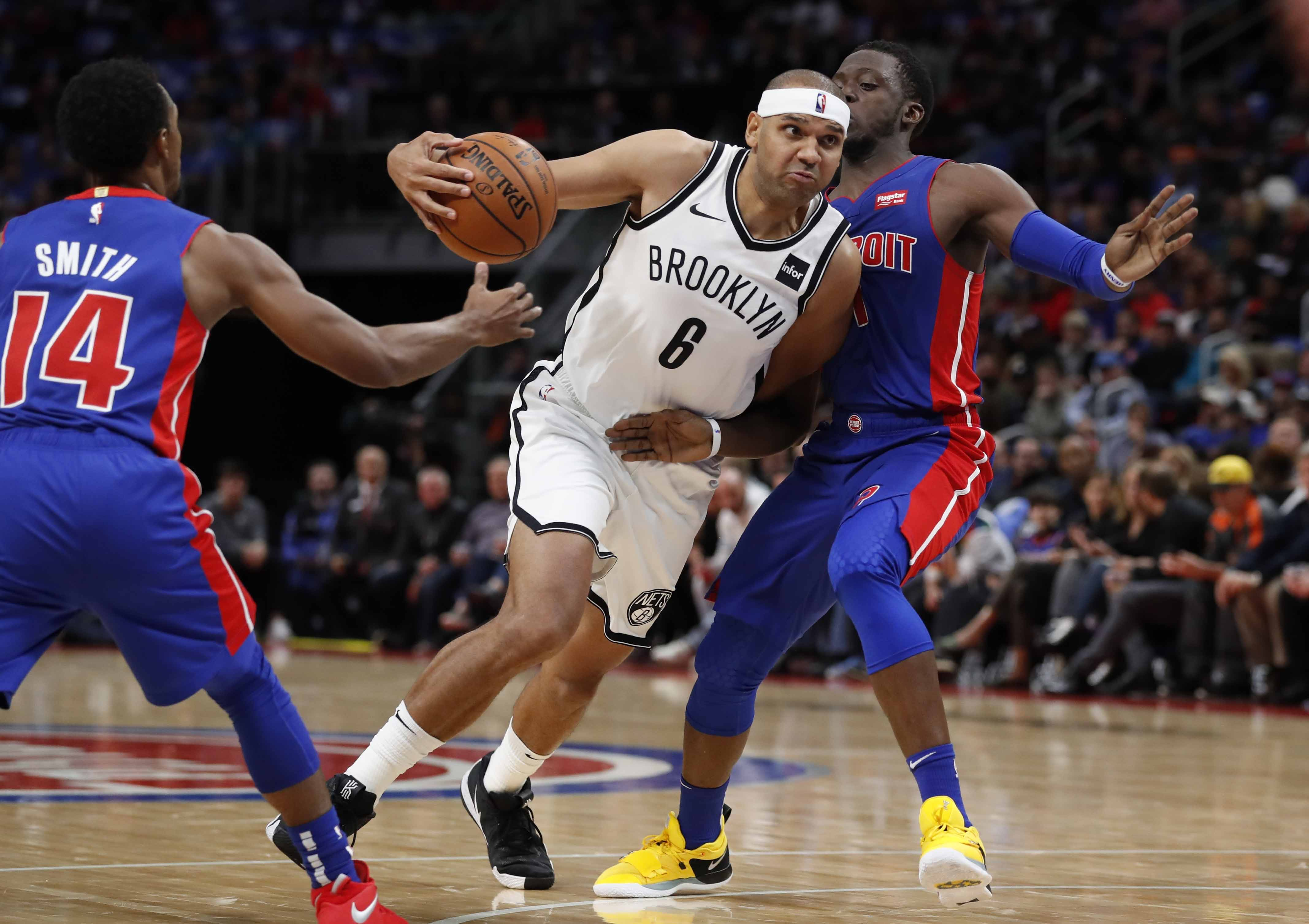 Brooklyn Nets forward Jared Dudley (6) drives between Detroit Pistons guards Ish Smith (14) and Reggie Jackson (1) during the first half of an NBA basketball game in Detroit on Wednesday.