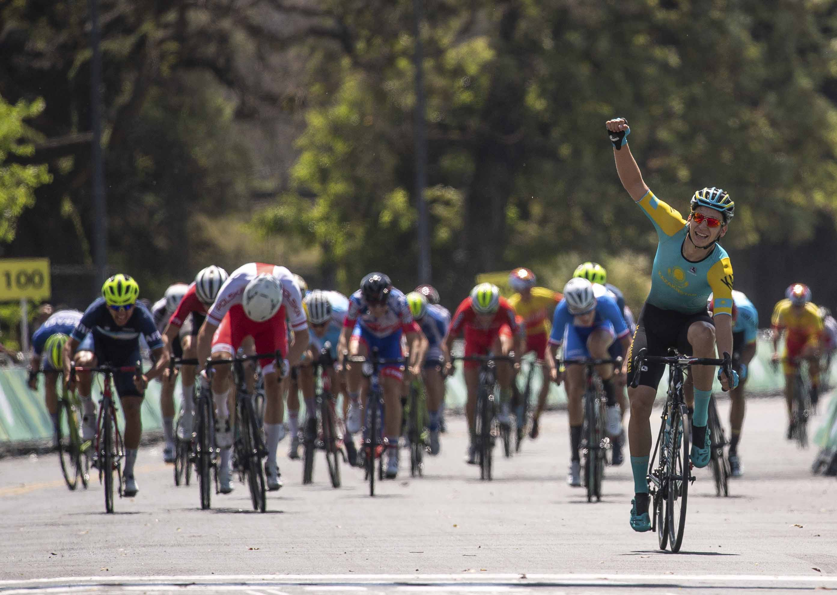 In this photo provided by the OIS/IOC, Gleb Brussenskiy of Kazakhstan celebrates his team's gold medal win as he finishes in the Cycling Men's Combined Criterium at Bosques de Palermo, during the Youth Olympic Summer Games in Buenos Aires, Argentina on Wednesday
