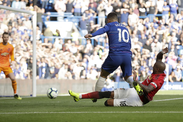 ManU midfielder Ashley Young tackles Chelsea's Eden Hazard during their English Premier League soccer match between Chelsea and Manchester United at Stamford Bridge stadium in London on Saturday.