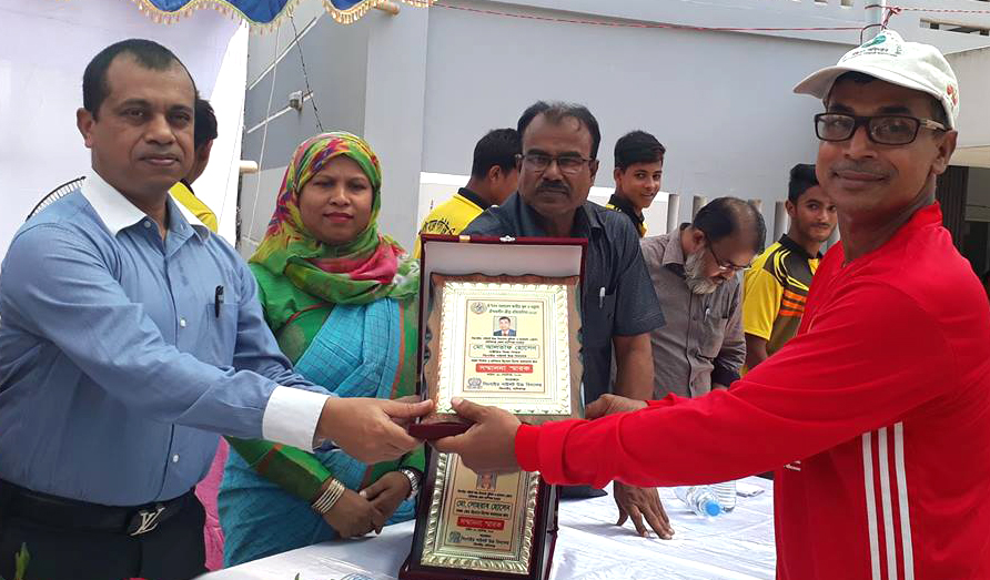 Deputy Commissioner of Manikganj District SM Ferdous (left) handing over the crest of honour to Coach and former national athlete Md Altaf Hossain at Singair Pilot High School premises in Manikganj District recently. Singair Pilot High School became champions in the Handball & Football Competitions of Manikganj District under training of Md Altaf Hossain.