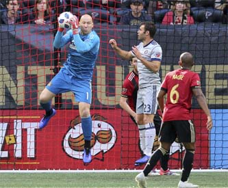 Atlanta United goalkeeper Brad Guzan (left) blocks a shot in front of Chicago Fire forward Nemanja Nikolic during the second half of an MLS soccer match in Atlanta on Sunday.