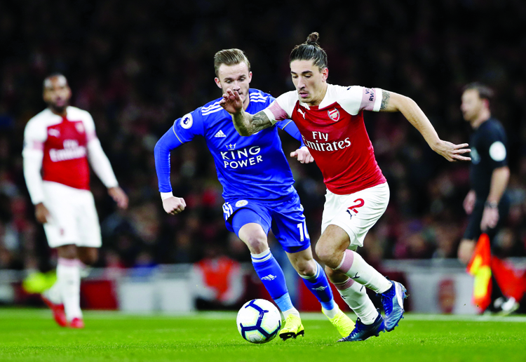 Leicester City's James Madison (left) vies for the ball with Arsenal's Hector Bellerin during the English Premier League soccer match between Arsenal and Leicester City at the Emirates stadium in London on Monday.