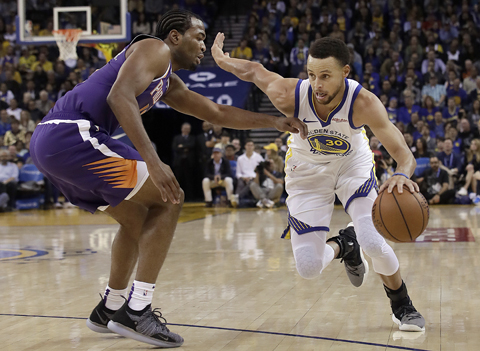 Golden State Warriors guard Stephen Curry (righ) drives against Phoenix Suns forward TJ Warren during the second half of an NBA basketball game in Oakland, Calif on Monday.