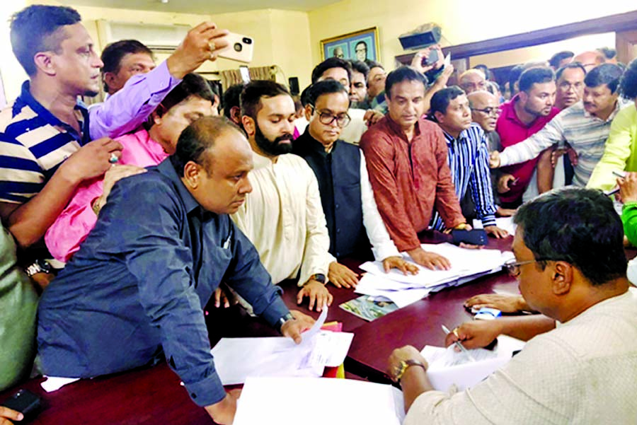 Hazi Mohammad Selim and his son Soleman Selim submitting nomination forms for the Parliamentary Election in Dhaka-7 constituency at the Awami,League office in the city's Dhanmondi on Monday.