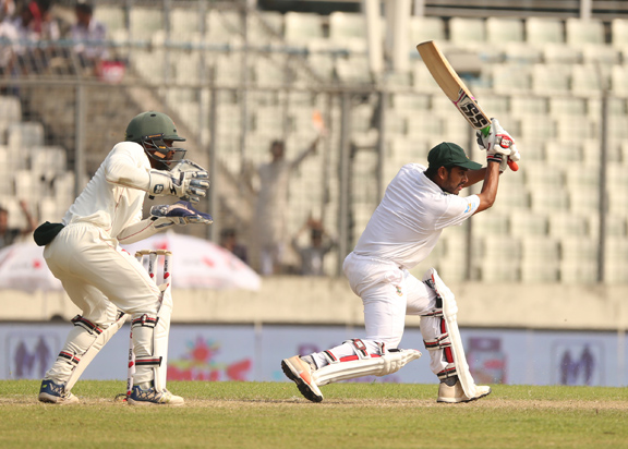 Mehidy Hasan Miraz (right) of Bangladesh plays a shot while Zimbabwean Wicketkeeper Regis Chakabva looks on during the second day play of the            second Test between Bangladesh and Zimbabwe at the Sher-e-Bangla National Cricket Stadium in the city's Mirpur on Monday.