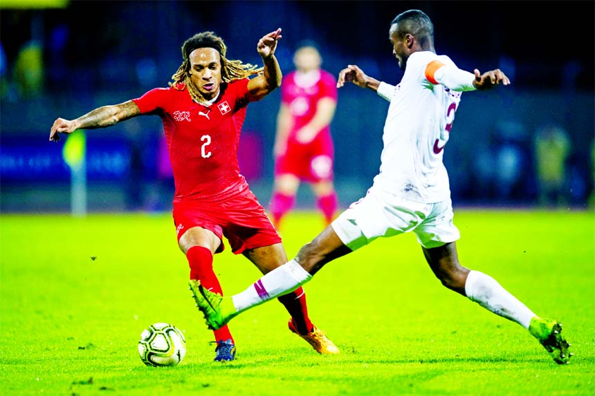 Switzerland`s Kevin Mbabu (left) is challenged by Qatar's Abdelkarim Hassan during an international friendly soccer match between Switzerland and Qatar at the Cornaredo stadium in Lugano, Switzerland on Wednesday.