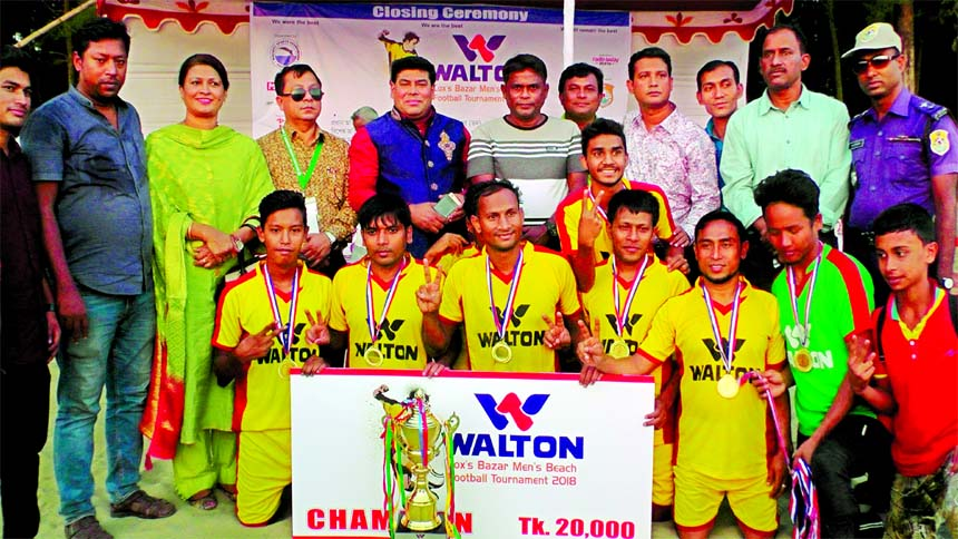 Youngmen\'s Club, the champions of the Walton 5th Men\'s Beach Football Tournament with the guests and officials of Cox\'s Bazar District Sports Association pose for a photo session at the Suganda Point in Cax\'s Bazar Sea Beach on Thursday.