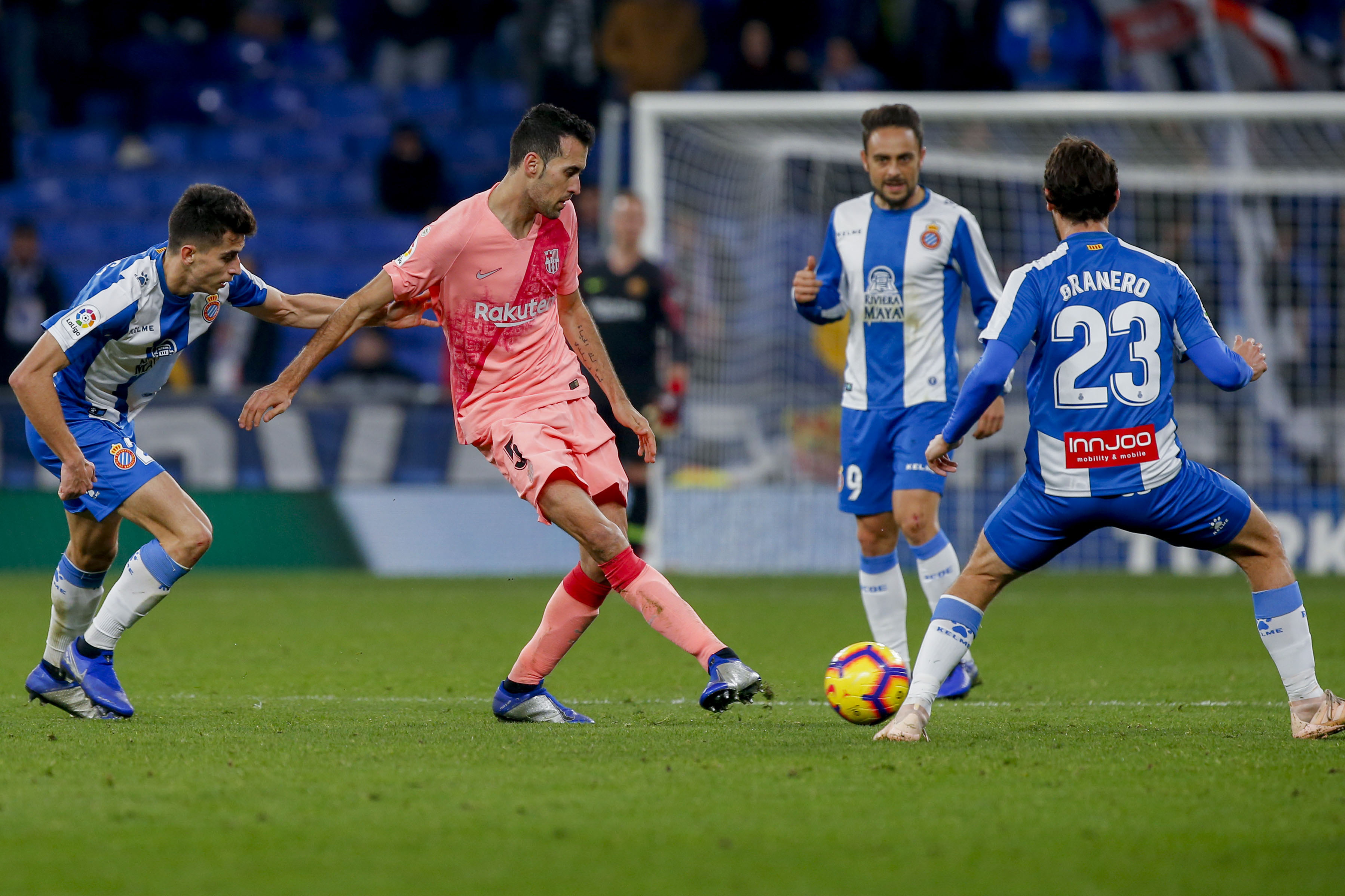 FC Barcelona midfielder Sergio Busquets (center) kicks the ball through RCD Espanyol forward Granero (23) during the Spanish La Liga soccer match between Espanyol and FC Barcelona at RCDE stadium in Cornella Llobregat, Spain on Saturday.