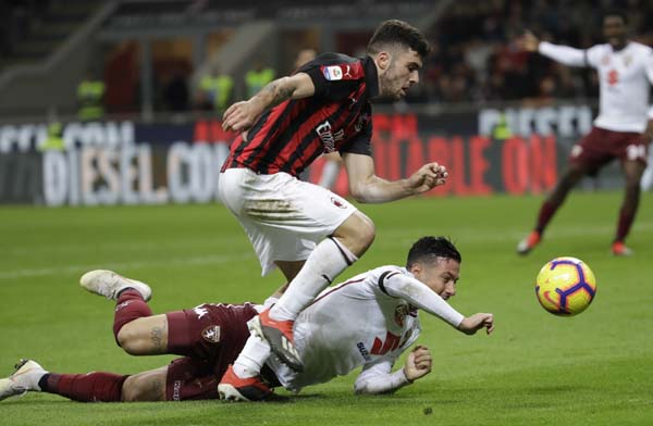 AC Milan's Patrick Cutrone, challenges for the ball with Torino's Armando Izzo during a Serie A soccer match between AC Milan and Torino , at the San Siro stadium in Milan, Italy on Sunday.