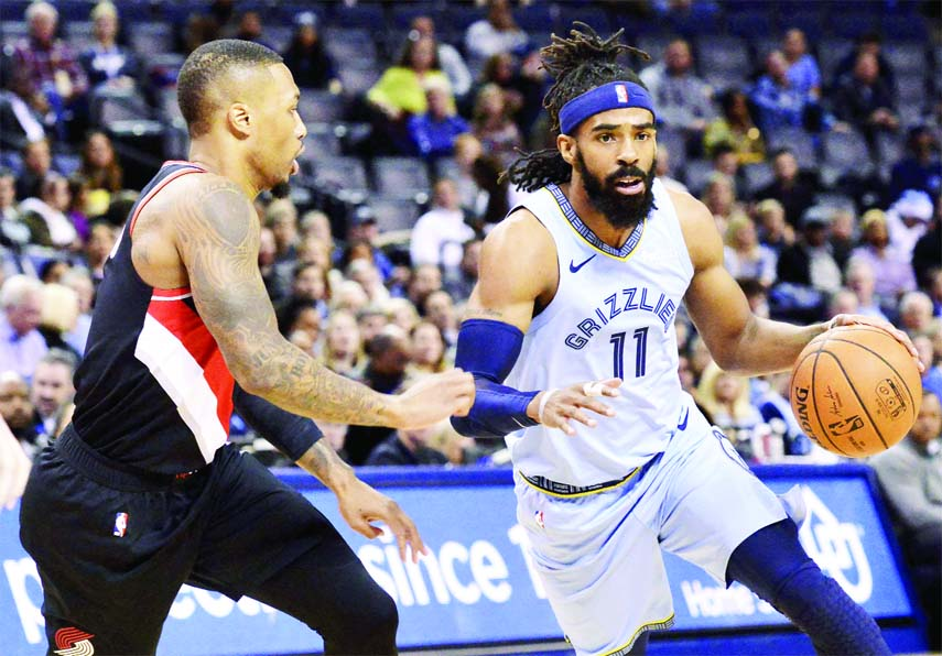 Memphis Grizzlies guard Mike Conley (11) drives against Portland Trail Blazers guard Damian Lillard in the first half of an NBA basketball game in Memphis on Wednesday.