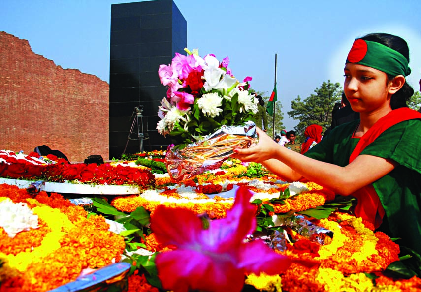 A tiny girl wearing national flag as headgear placing wreaths at the Martyred Intellectuals Memorial at Mirpur on Friday.