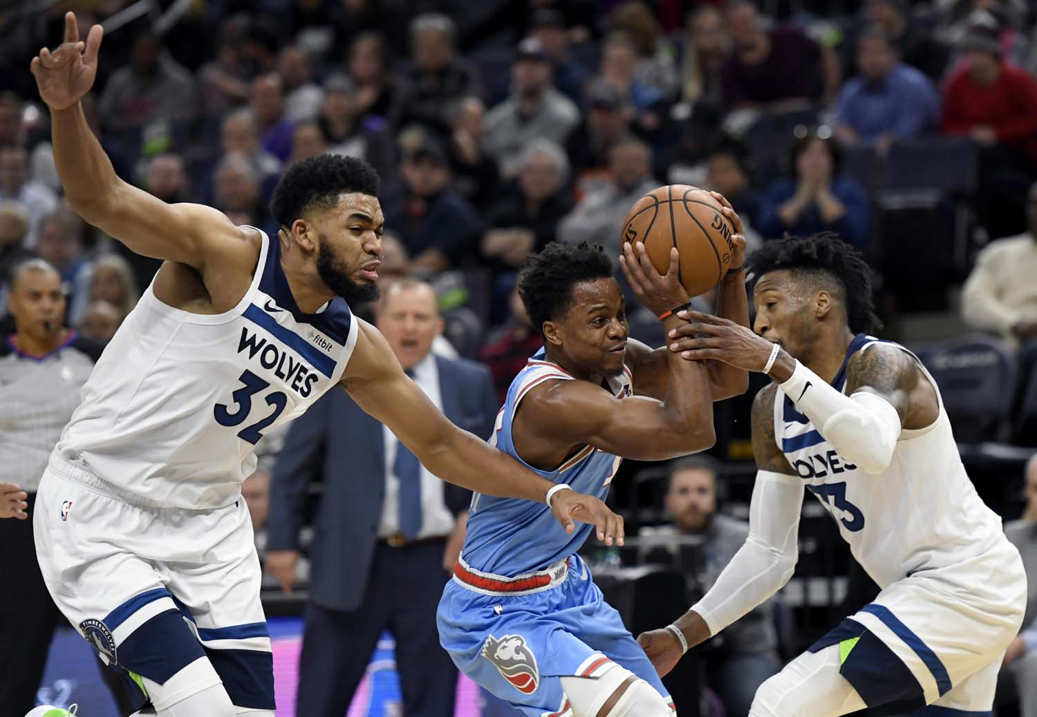 Minnesota Timberwolves' Robert Covington (33) fouls Sacramento Kings' Yogi Ferrell (3) as Minnesota Timberwolves' Karl-Anthony Towns (32) helps guard during the third quarter of an NBA basketball game on Monday.