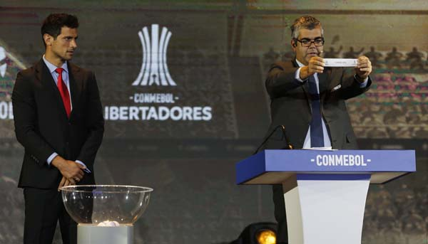 Conmebol Competition Secretary Fred Nantes holds up the name of Brazil's Flamengo during the drawing ceremony for the Copa Libertadores soccer tournament in Luque, Paraguay on Monday. At left is Paraguay's soccer player Roque Santa Cruz.