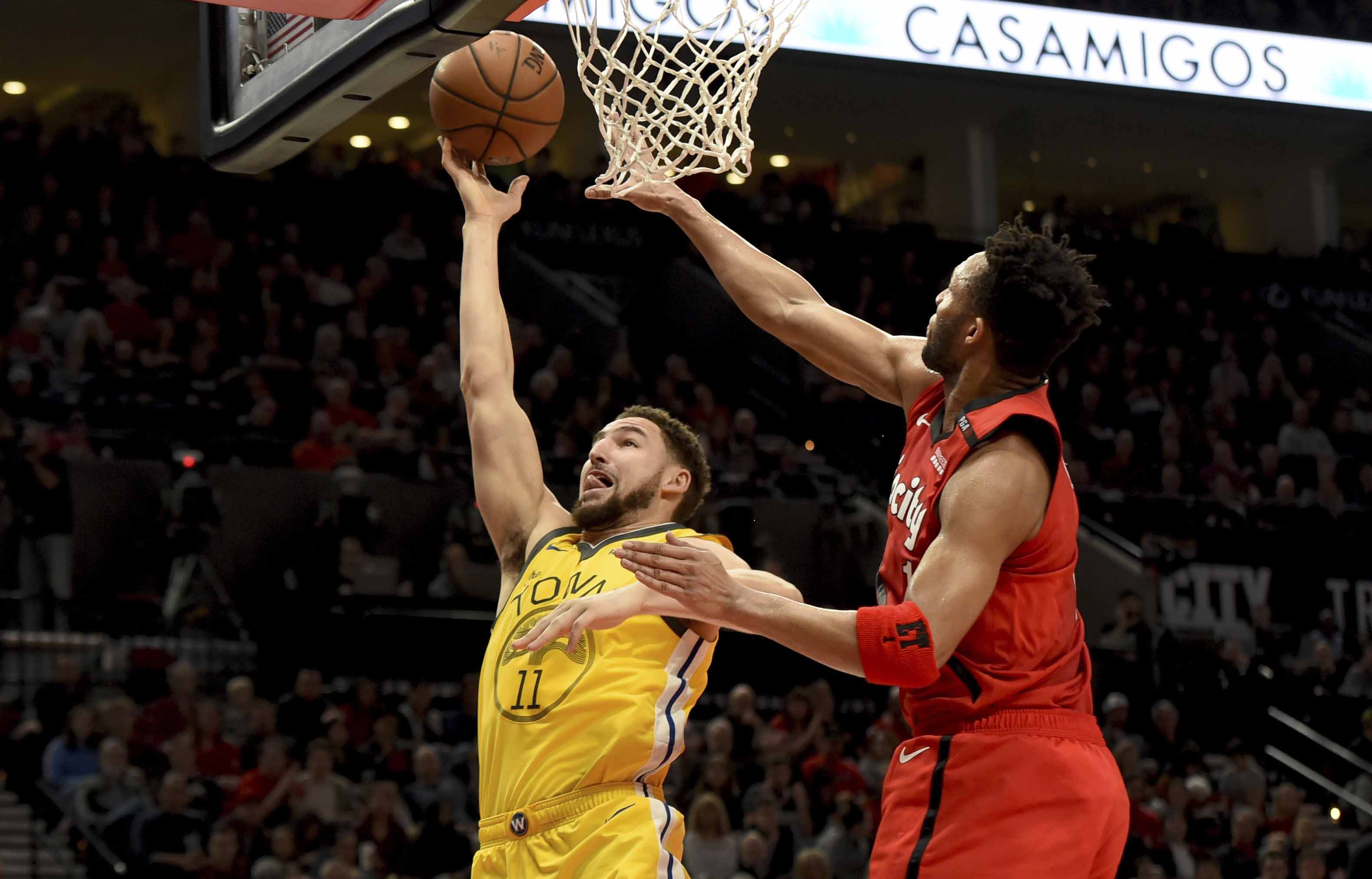 c8b62807b6be Golden State Warriors guard Klay Thompson (left) drives to the basket on  Portland Trail Blazers guard Evan Turner (right) during the first half of  an NBA ...
