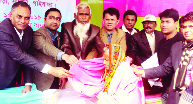 SAGHATA (Gaibandha): Uzzal Kumar Gosh, UNO, Saghata Upazila distributing blankets among the cold-hit people at Char Gobindapur Dakhil Madrasa in Haldia Union recently.