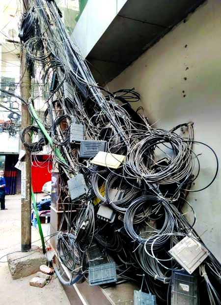Keeping extra internet cables in open places on the main roads by service providers have become a common phenomenon, causing sufferings to pedestrians. This photo was taken from Motijheel area on Tuesday.