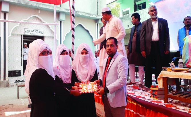 DAMUDYA (Shariatpur): Industrialist Alhaj Khaledur Rahman Sikder, President, Managing Committee of Hamidiya Kamil Madrasa at Damudya Upazila  receiving  prize from the Kamil examinees at the farewell programme as Chief Guest yesterday.