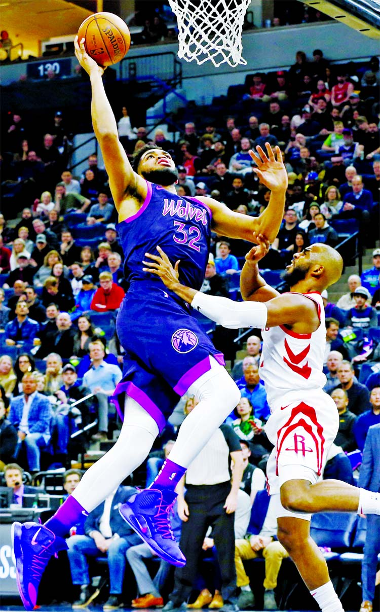 Minnesota Timberwolves' Karl-Anthony Towns (left) goes in for a layup as Houston Rockets' Chris Paul defends in the first half of an NBA basketball game in Minneapolis on Wednesday.