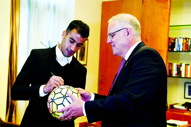 Refugee Hakeem al-Araibi (left) signs a ball for Australian Prime Minister Scott Morrison at Parliament House in Canberra, Australia on Thursday. Al-Araibi was detained in Thailand for three months under threat of extradition to Bahrain and has come to Canberra to shake hands with the Prime Minister and say thank you for his freedom.