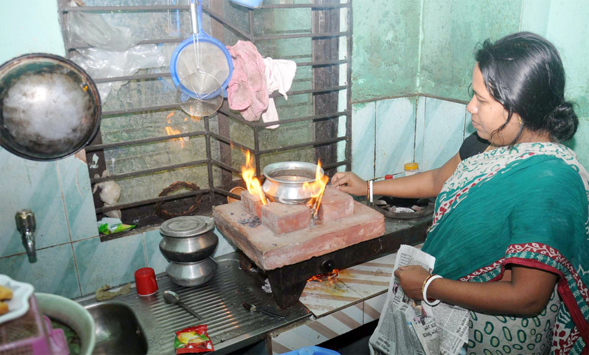 A housewife  at Eidgah area using brick burner for cooking as gas crisis hits the Port City yesterday.