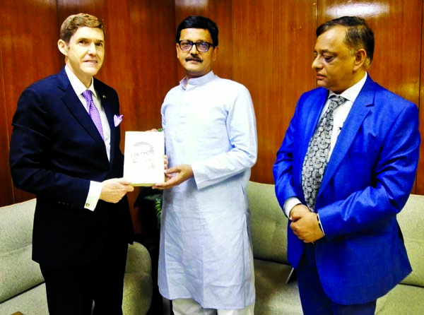 State Minister for Shipping Khalid Mahmud Chowdhury handing over a book titled 'Bangabandhur Asamapta Atmajibani' to US Envoy to Bangladesh Earl Robert Miller when the latter called on the minister at the Secretariat on Wednesday.
