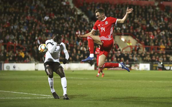 Trinidad and Tobago's Aubrey David (left) and Wales' Ryan Hedges battle for the ball during the International Friendly soccer match between Wales and Trinidad and Tobago, at the Racecourse Ground, in Wrexham, Wales on Wednesday.