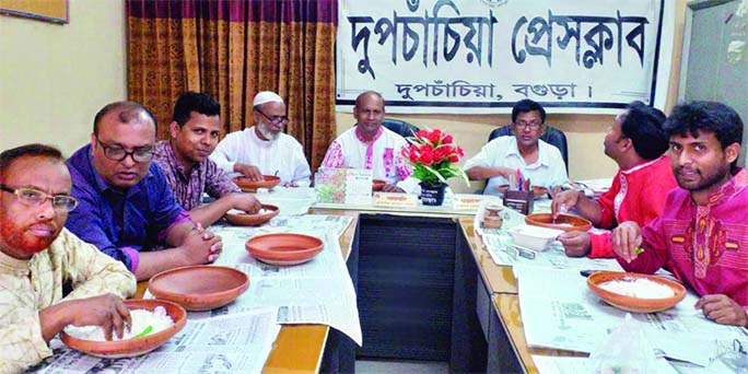 DUPCHANCHIA (Bogura):  Leaders of Dupchanchia Press Club eating 'panta' and  hilsa marking the Pahela Baishakh at the Club premises on Sunday.