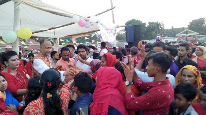 M A Latif MP greeting people by giving pitha marking the Pahela Baishakh on Sunday.