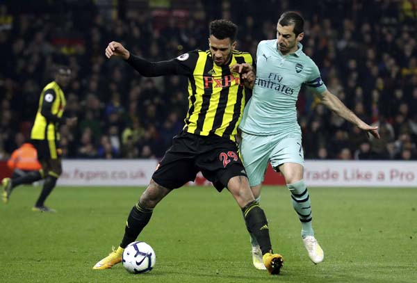 Arsenal's Henrikh Mkhitaryan (right) vies for the ball with Watford's Etienne Capoue during the English Premier League soccer match between Watford and Arsenal at Vicarage Road stadium in Watford, England on Monday.