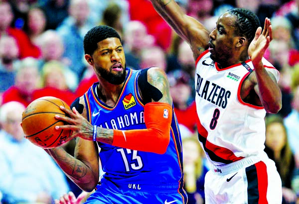 Oklahoma City Thunder forward Paul George (left) looks to pass the ball around Portland Trail Blazers forward Al-Farouq Aminu during the first half of Game 2 of an NBA basketball first-round playoff series in Portland, Ore on Tuesday.