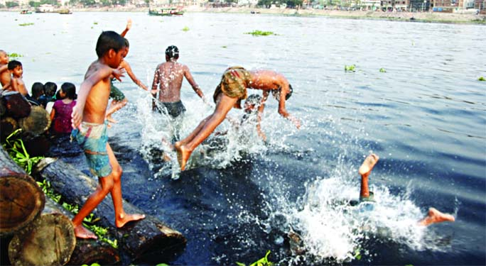 Children jump into the stinky water of the Buriganga River during a hot-summer day taking risk of life. The photo was taken from riverbank at Kamrangirchar in Dhaka on Friday.