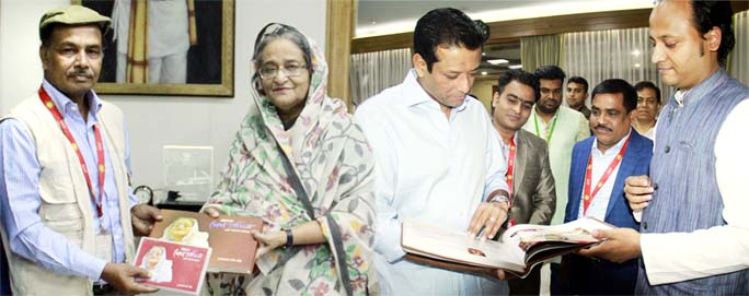 A  photo album titled  'Sheikh Hasina in Chattogram ' handing  over to Prime Minister Sheikh Hasina and her son Sajeeb Wazed Joy at a  simple ceremony at Prime Minister Office by senior photo journalist and freedom fighter Debu Prasad Das  recently.