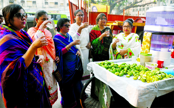 To cool themselves a group of women taking lemon sharbat, allegedly made of impure water from a street vendor amid Thursday's sweltering heat. This photo was taken from in front of Jatiya Press Club.
