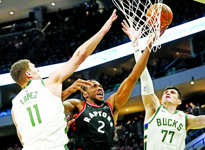 Toronto Raptors' Kawhi Leonard shoots between Milwaukee Bucks' Brook Lopez and Ersan Ilyasova during the second half of Game 2 of the NBA Eastern Conference basketball playoff finals in Milwaukee on Friday. The Bucks won 125-103 to take a 2-0 lead in the series.