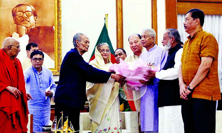 Prime Minister Sheikh Hasina being greeted with bouquet by the leaders of Buddhist community at Ganobhaban on Monday on the occasion of Buddha Purnima , a religious festival of the community.