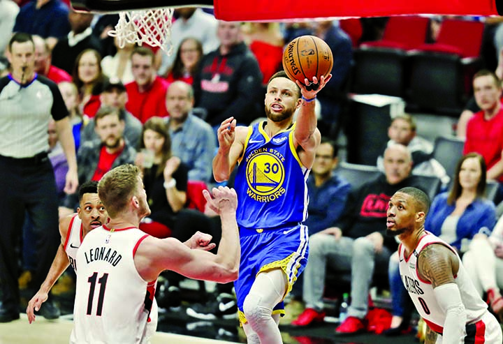 Golden State Warriors guard Stephen Curry (30) puts up a shot against Portland Trail Blazers forward Meyers Leonard (11) during the second half of Game 4 of the NBA basketball playoffs Western Conference finals  in Portland, Ore on Monday. The Warriors won 119-117 in overtime.