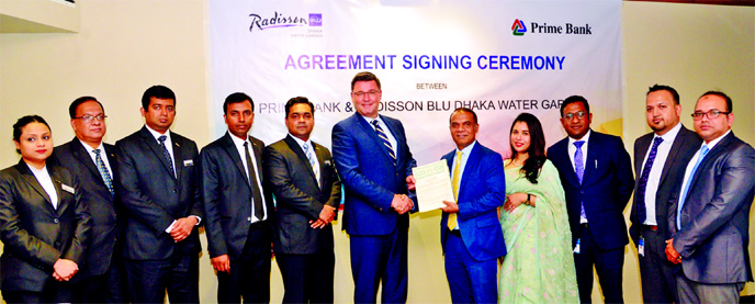 Zubayer Ershad, Head of Consumer Banking Business of Prime Bank Ltd and Alexander Haeusler, General Manager of Radisson Blu Dhaka Water Garden, exchanging an agreement signing document at a hotel in the city recently.  Shaila Abedin, Head of Segments of the Bank was present. Under the deal, Prime Bank's Platinum, World MasterCard and Monarch (Priority banking) Prestige Card holders will enjoy Buy One Get One (BOGO) offer on buffet breakfast, lunch and dinner round the year.