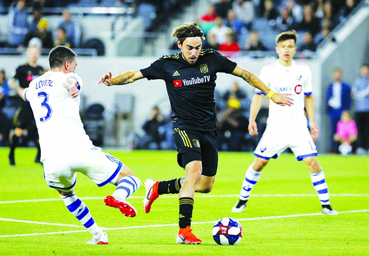 Los Angeles FC (LAFC) midfielder Andre Horta (center) vies with Montreal Impact defender Daniel Lovitz (3) for the ball during the second half of an MLS soccer match in Los Angeles on Friday. LAFC won 4-2.