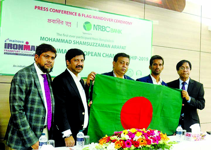 Tamal SM Parvez, Chairman of NRBC Bank Ltd, hands over the national flag to Mohammad Samsuzzaman Arafat, a participant of Ironman European Championship, Frankfurt 2019, in a media briefing at the bank's headquarters in city on Tuesday. NRBC is sponsoring Arafat to attend the event under its CSR activities.